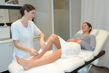 woman getting her leg waxed at beauty spa