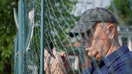 Man Near a Metallic Fence Text Using a Smartphone