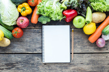 Top view of empty notebook with fruits and vegetables on the old wood table with copy space