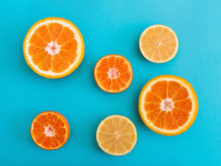 Citrus fruit Flat lay Halves of orange, lemon and mandarin are lying on bright blue background Photo template in top view