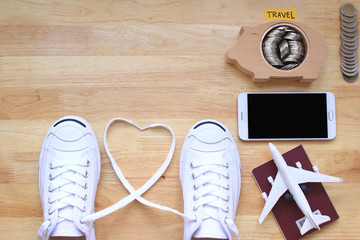 Saving planning for Travel budget of holiday concept, White sneakers shoes and airplane on passport with a smartphone and stack of coins money in piggy bank wood on the table background