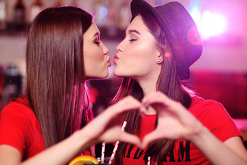 two cute lesbian girlfriends kissing on bar background at a party