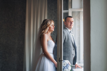 Beautiful bride and groom with curly hair stand near the window in the studio. Portrait of stylish newlyweds.