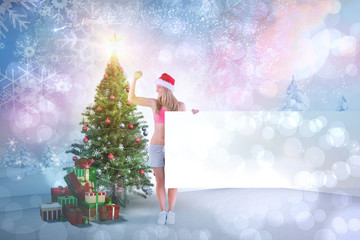 Festive fit blonde showing poster against snowy landscape with fir trees