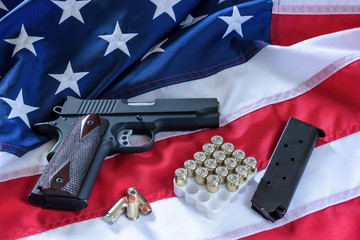 The second amendment and gun control in the US, concept. A handgun, a magazine, bullets, and the american constitution on the USA flag.