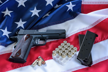 The second amendment and gun control in the US, concept. A handgun, magazines, bullets, and the american constitution on the USA flag.