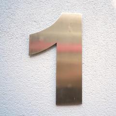 """Hausnummer """"1"""" an der Fassade eines Hauses"""