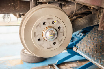tyre replacement service, Car brake without wheels at auto repair shop