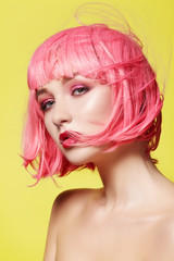 Young woman in pink wig. Beautiful model with fashion makeup. Bright spring look. Sexy hair color, medium hairstyle