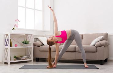 Woman training yoga in triangle pose