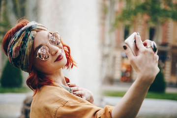 beautiful young woman wearing round sunglasses taking a selfie picture outdoors. hippie fashion blogger on vacation, taking self portrait with a smartphone. street style, music festival portrait.