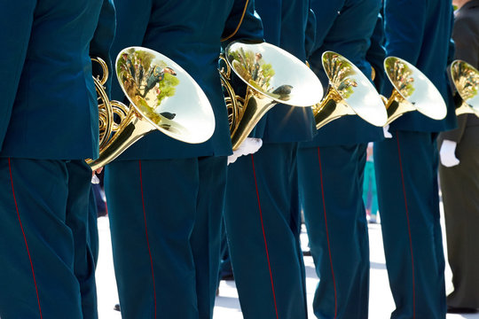 Closeup military musicians in green uniform and white gloves stand with French horns on the square during the parade of the orchestra on the street.