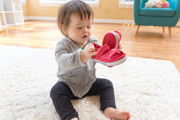 Happy toddler boy playing with his shoes in his house