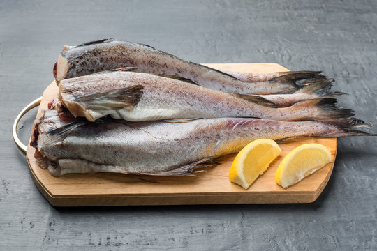Slave raw Fish on wooden cutting Board on dark background Lemon and Pepper mix