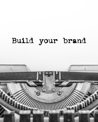 Build your brand text typed on a vintage typewriter in black and white. close-up. on white old paper