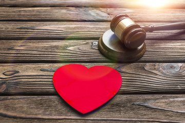 heart made of wood, hammer of a judge on a wooden background. family law, divorce. conflicts.