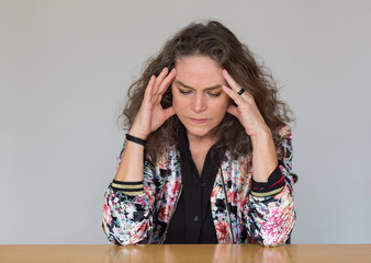 Worried woman deep in thought frowning in concentration as she rests her head on her hands sitting at a table