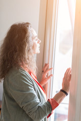 Attractive middle-aged woman enjoying the warmth of the sunlight as she stands in front of a window with closed eyes and a blissful expression