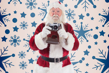 Santa is taking a picture against snowflake pattern