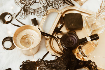 Black and Gold Woman's accessories on gold tray. Beauty, fashion blogger concept