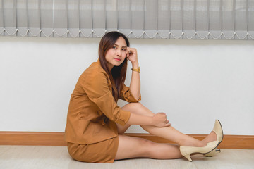 Portrait of beautiful asian business woman wear yellow dress sit in a office,Thailand people wear ladies uniforms office