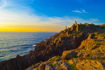 Cadres-photo bureau Cote Picturesque seascape with lighthouse, cliffs, rocks and stacks in beautiful sunset