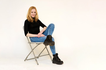 Portrait of a beautiful blonde girl in jeans sitting on a chair on a white background