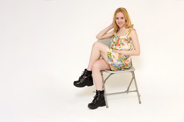 Portrait of a beautiful blond girl on a white background sitting on a chair in a dress.