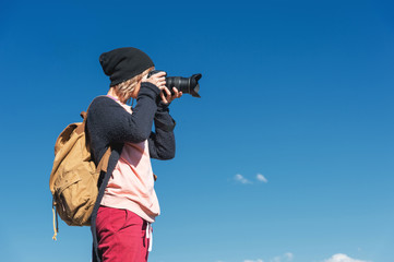 Portrait of a stylish girl hippy in a hat and with a backpack that takes pictures of her on a DSLR camera outdoors against a blue sky on a sunny afternoon. The concept of photography in travel