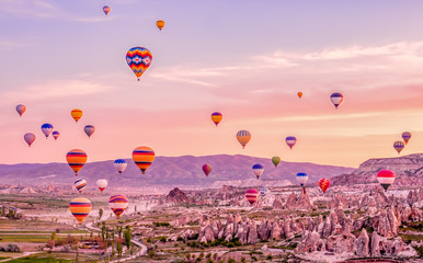 Fototapeten Ballon Colorful hot air balloons flying over rock landscape at Cappadocia Turkey