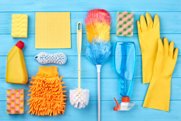 Colorful equiment for cleaning. Set of cleaning products on blue wooden background.