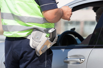 Police officer is checking the driving license of a car driver during a traffic control