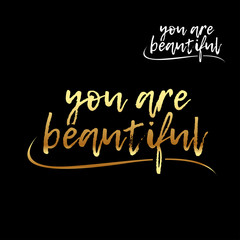 You are beautiful golden letters card. Hand drawn lettering background. Ink illustration. Modern brush calligraphy. Isolated on black background. Compliment for women.