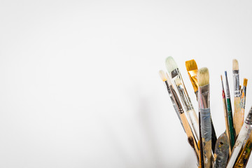 Art equipment: easel, brushes, tubes with paint, palette and paintings