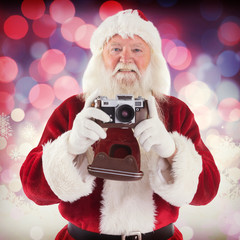 Santa is taking a picture against glowing christmas background