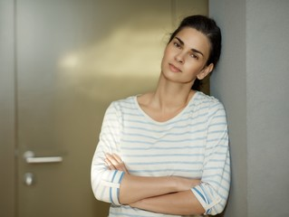 Confident woman leaning against wall