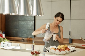 Sporty woman drinking shake in kitchen at home