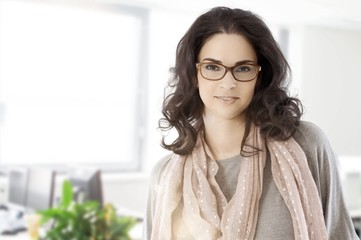 Portrait of adult woman in glasses at the office