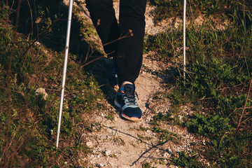 Hiking on the mountain with sticks, feet on a footpath close-up
