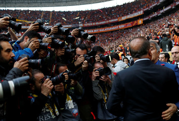 Photographers take pictures as the coaches Terim of Galatasaray and Gunes of Besiktas chat before kick off during the Turkish Super League soccer match between Galatasaray and Besiktas at Turk Telekom Arena in Istanbul