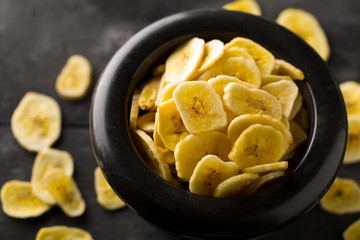 Heap of dried banana chips snack in black bowl on rustic table