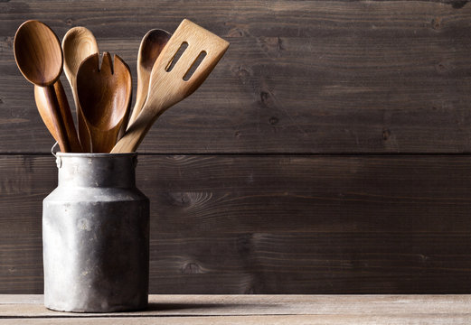 Wooden kitchen cooking tools with spoons and spatula in front of rustic wooden board background