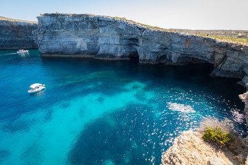 Obraz Exploring the dramatic huge cliffs and sea caves of east coast of Comino, over looking the deep azure crystal clear waters of the Mediterranean, Comino, Malta, June 2017 - fototapety do salonu