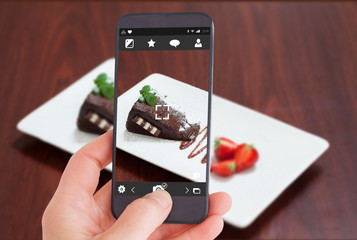 Female hand holding a smartphone against front view of chocolate cake with strawberries