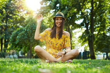 Happy woman outdoor in summer sitting on grass