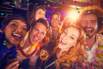 Group of friends having fun in bar against flying colours