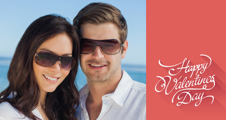 Smiling couple wearing sunglasses and looking at camera against happy valentines day