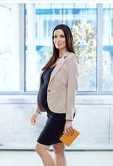 Happy pregnant woman in business casual in office