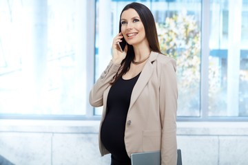 Happy pregnant woman in on the phone in office