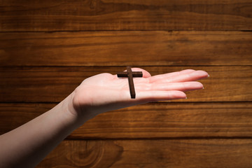 Hand showing against overhead of wooden planks